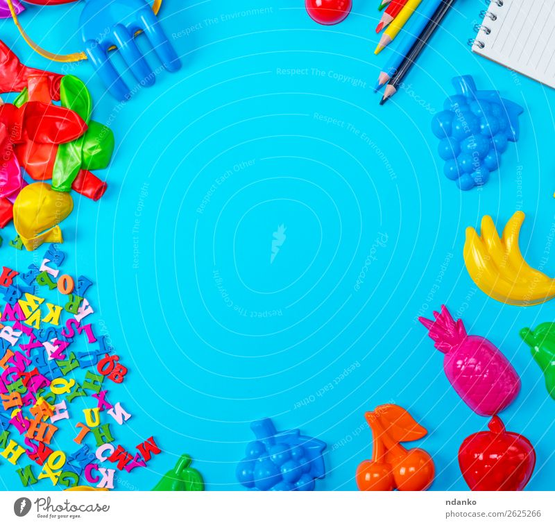 Blue background with childrens plastic toys Playing School Business Paper Pen Toys Balloon Wood Plastic Above Clean Yellow Red White Colour notebook education