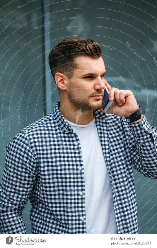 Young man talking on the mobile Lifestyle Hair and hairstyles Leisure and hobbies To talk Telephone PDA Technology Human being Man Adults T-shirt Beard Observe