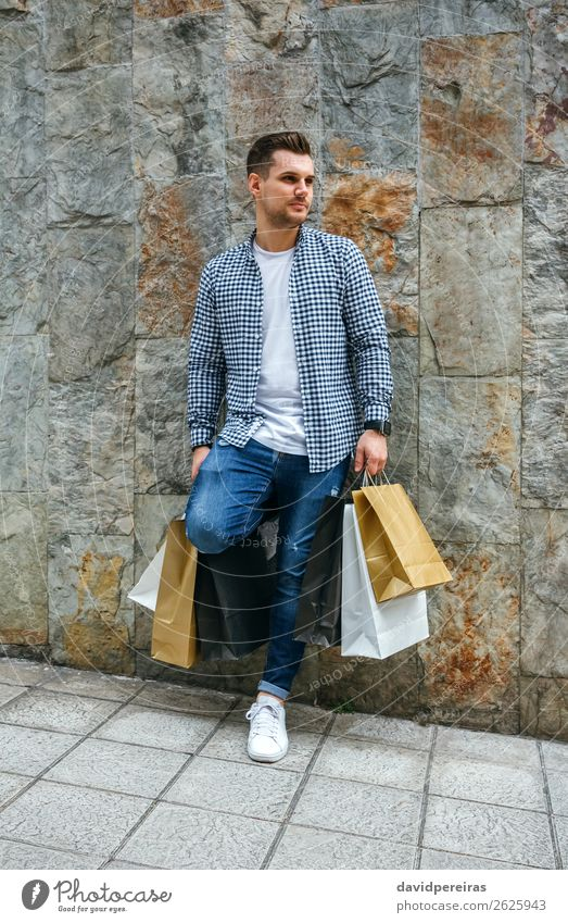 Young man with shopping bags Lifestyle Shopping Hair and hairstyles Relaxation Leisure and hobbies Human being Man Adults Fashion T-shirt Jeans Sneakers Stand