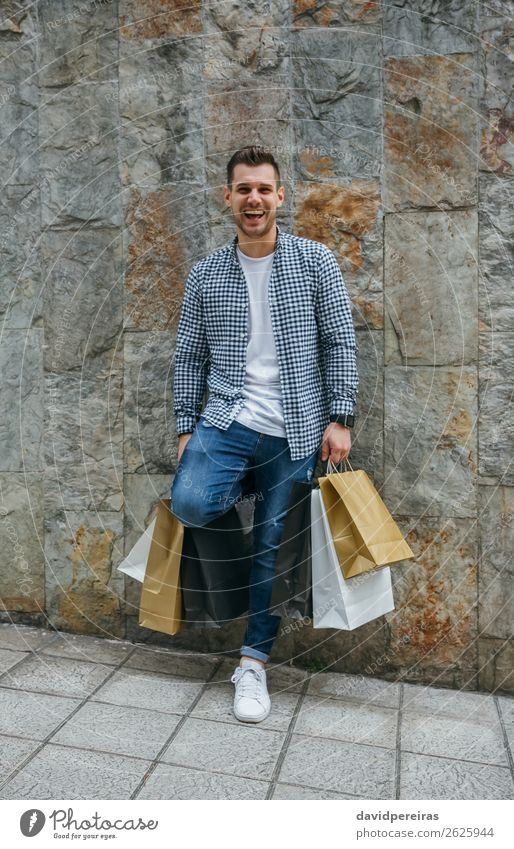 Young man with shopping bags Lifestyle Shopping Happy Hair and hairstyles Relaxation Leisure and hobbies Human being Man Adults Fashion Jeans Sneakers Smiling