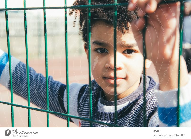 Little boy leaning at the metal fence of the playground Child School Boy (child) Hand Autumn Playground Metal Small Black Protection Safety (feeling of) Fence