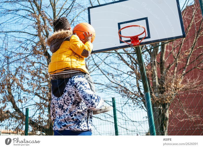 Little boy on daddy´s shoulder playing basketball Joy Happy Relaxation Leisure and hobbies Playing Winter Sports School Boy (child) Parents Adults Father