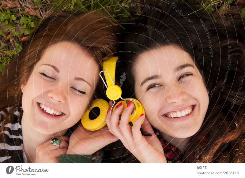 Teen girls sharing music lying in the grass Joy Beautiful Winter Music Headset Human being Woman Adults Friendship Youth (Young adults) Autumn Grass Leaf