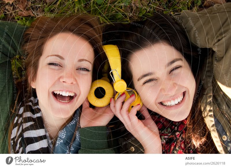 Two happy teenage girls lying on the grass sharing headphones to listen to music Joy Beautiful Winter Music Headset Human being Woman Adults Friendship
