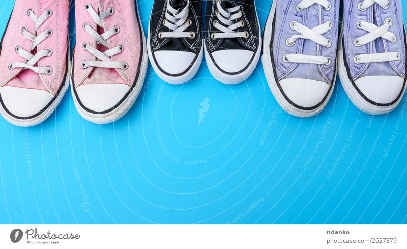 three pairs of textile worn shoes on a blue background Old Blue White Black Lifestyle Sports Style Copy Space Fashion Pink Design Retro Modern Dirty Footwear