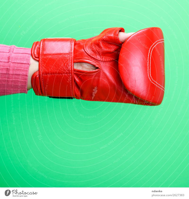 hand is wearing a red leather boxing glove on a green background Sports Woman Adults Hand Leather Gloves Fitness Green Red Protection Colour Competition