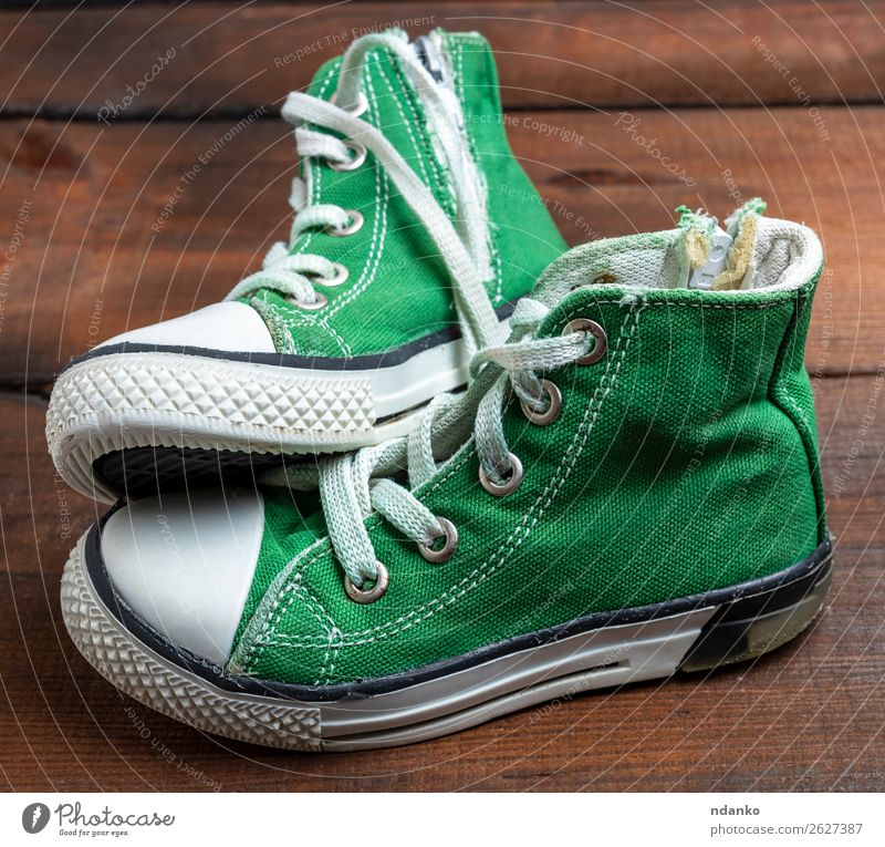 pair of worn green textile sneakers Old Green White Black Lifestyle Wood Sports Style Small Fashion Design Modern Dirty Footwear Fitness Clothing