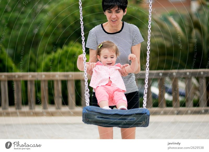 Mother swinging her little daughter on a swing Lifestyle Joy Happy Beautiful Leisure and hobbies Playing Summer Climbing Mountaineering Child Human being
