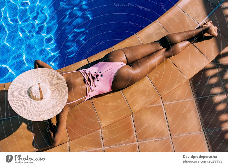 Black woman lying down in a swimming pool side African Anonymous Rear view Barefoot Beautiful Blue Copy Space Crops Ethnic Faceless Woman Girl Healthy