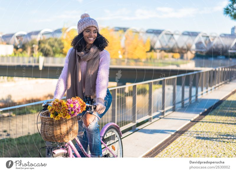 Black young woman riding a vintage bicycle Bicycle Vintage Basket Girl Woman Mixed race ethnicity Beautiful Retro Flower Happy Bouquet Winter Autumn
