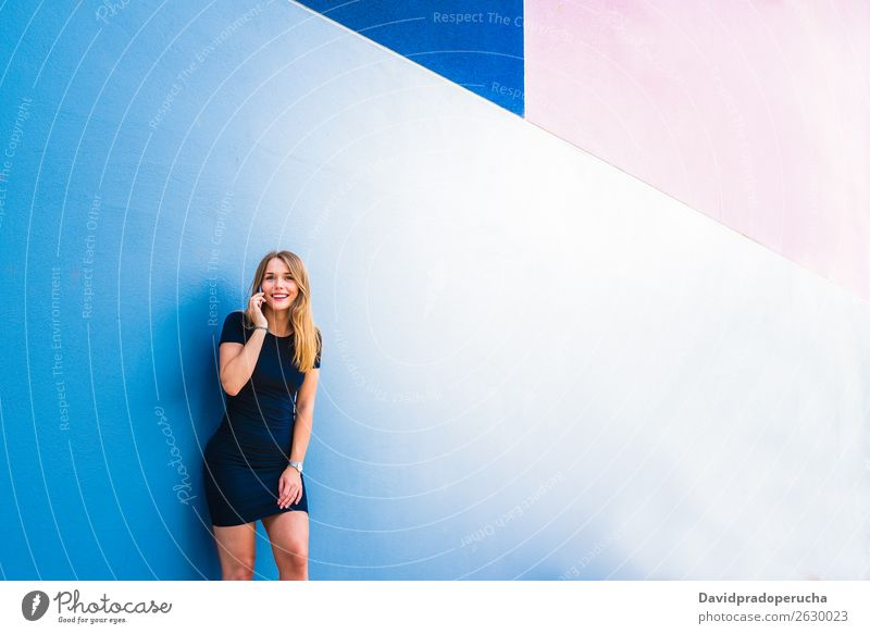 Happy young woman on the mobile phone by a colorful wall Woman Multicoloured Blonde Telephone Wall (building) Mobile Technology Dress