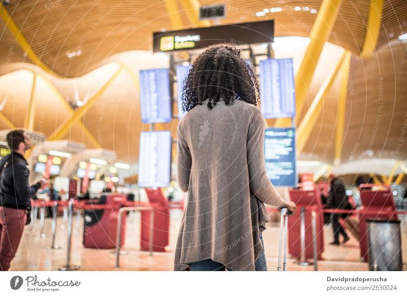 Black Woman looking at the timetable information panel in the airport with a suitcase Airport Timetable Display Human being Story Board International