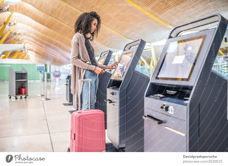 happy black woman using the check-in machine at the airport getting the boarding pass. Airport self Service Checkered Self-service Ticket Woman African American
