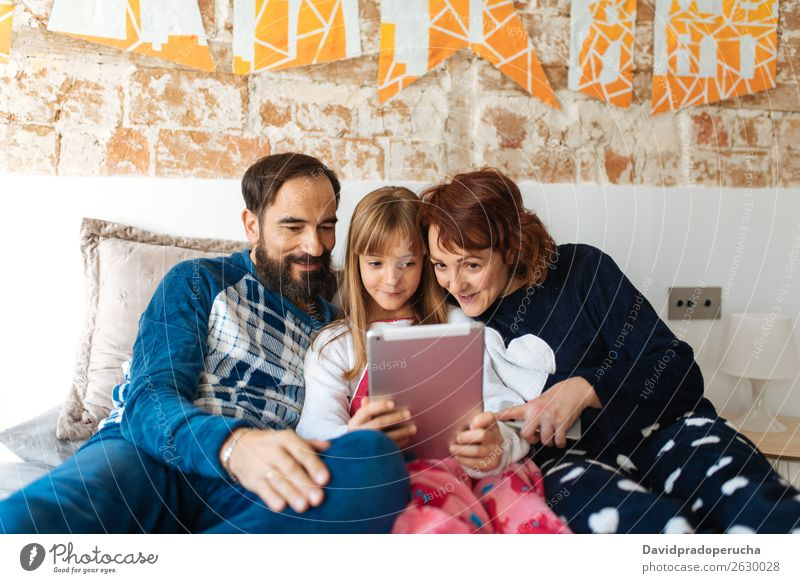 Couple relaxed at home in bed with their little daughter on the mobile phone and tablet Affection Bed Bedroom Wife Husband Daughter Child Mobile Telephone