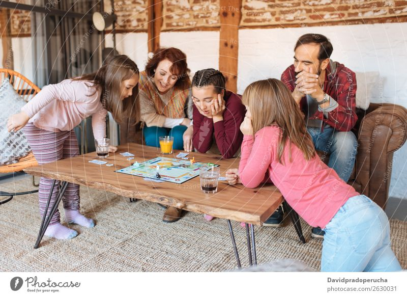 Happy family at home in the couch playing classic table games Family & Relations Table Playing Board Father Home Human being sisters Caucasian siblings Parents