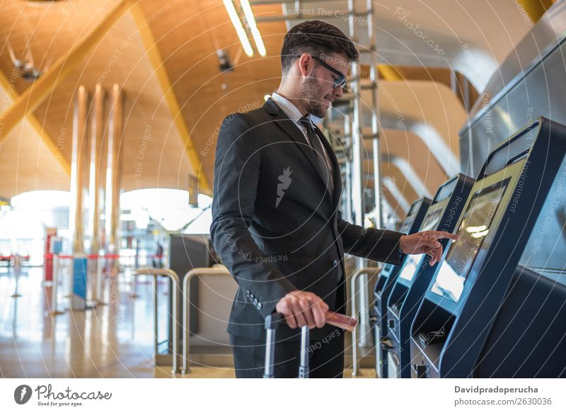 Young business man doing self check in a machine at the airport Airport Man Vacation & Travel Checkered Service Kiosk check-in Ticket Technology Wooden wall