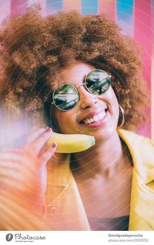 Surprised mixed race woman in a colorful artwork background wall playing with a banana Woman Mixed Close-up Portrait photograph Black Cheerful Banana Yellow