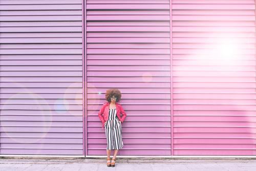 Mixed race woman in a multicolor wall background Woman Smiling Portrait photograph Black Lifestyle Background picture Multicoloured