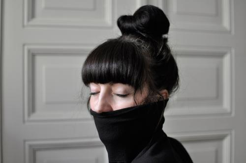 young woman with bangs, bun and closed eyes in turtleneck sweater Feminine Young woman Youth (Young adults) 1 Human being 18 - 30 years Adults Sweater