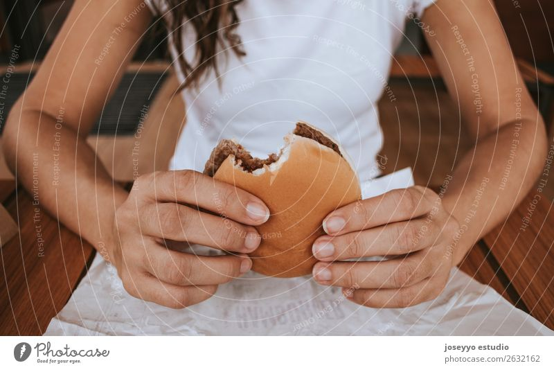 Young girl holding fast food burger Bread Roll Lunch Diet Fast food Lifestyle Vacation & Travel Human being Hand Street Fashion To hold on Delicious Appetite