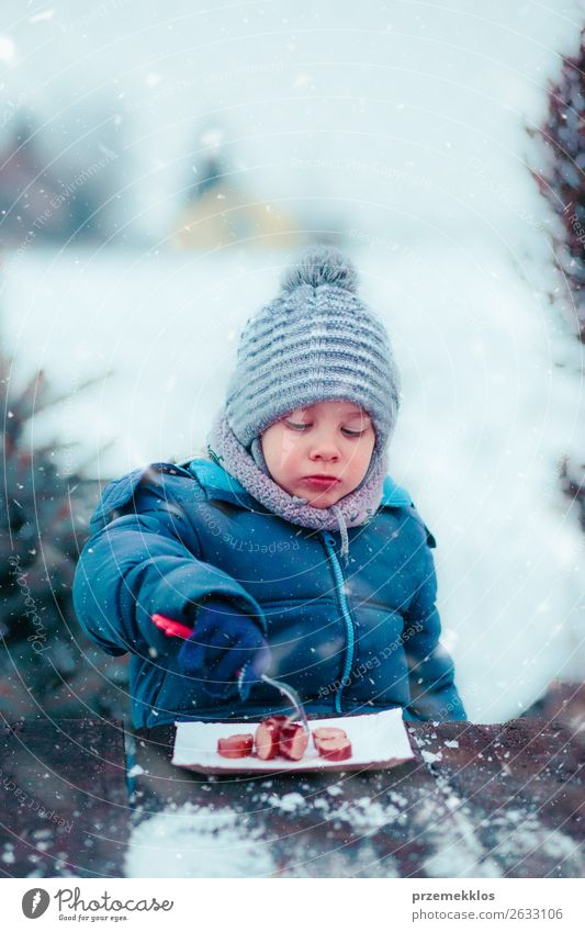 Boy eating roasted sausage on picnic outdoors in winter Sausage Eating Lifestyle Joy Winter Snow Winter vacation Boy (child) 3 - 8 years Child Infancy Snowfall