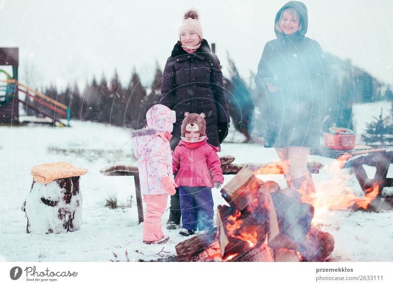 Family spending time together gathered around campfire Woman Child Human being White Joy Girl Winter Lifestyle Adults Snow Family & Relations Happy Garden