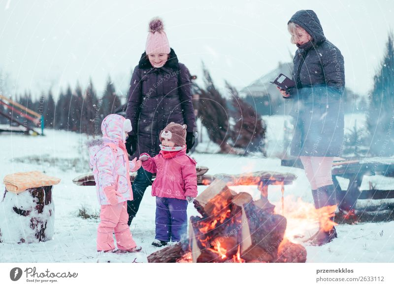 Family spending time together gathered around campfire Woman Child Human being White Joy Girl Winter Lifestyle Adults Snow Family & Relations Happy