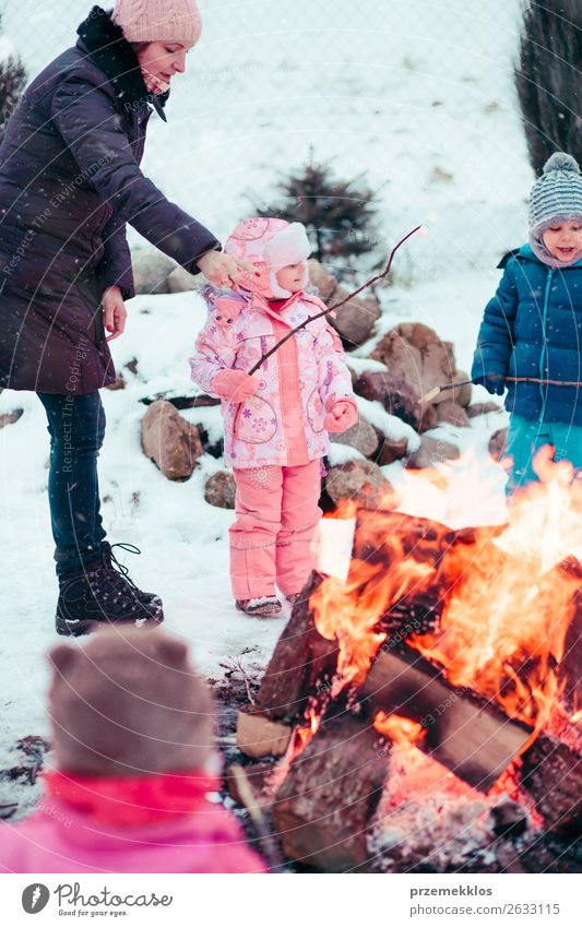 Family spending time together gathered around campfire Lifestyle Joy Happy Leisure and hobbies Winter Snow Winter vacation Garden Child Human being Girl