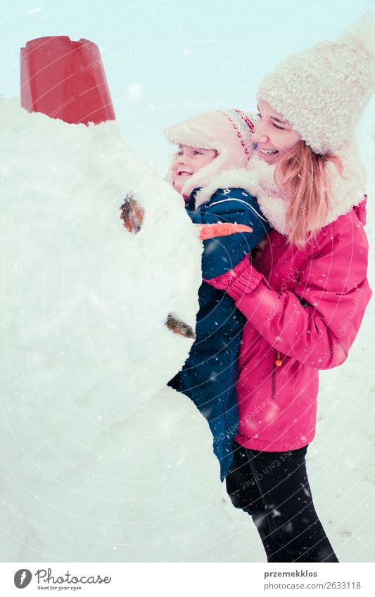 Girl and her little sister making a snowman Woman Child Human being Youth (Young adults) Young woman White Joy Winter Lifestyle Adults Snow Family & Relations