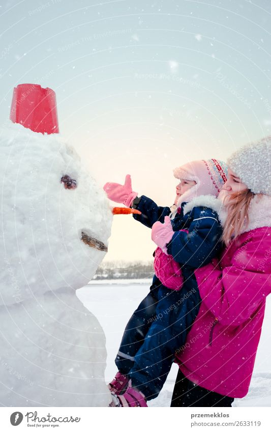 Girl and her little sister making a snowman Lifestyle Joy Happy Winter Snow Winter vacation Child Human being Young woman Youth (Young adults) Sister