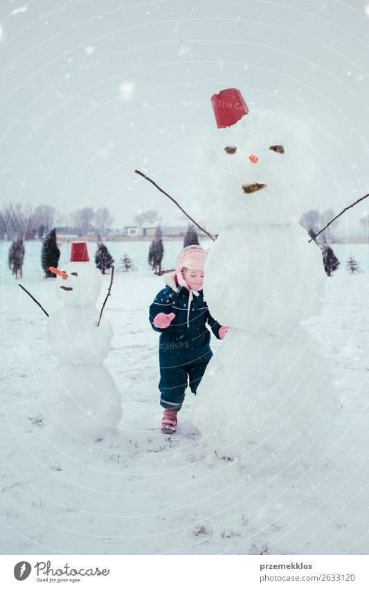 Little girl making a snowman Lifestyle Joy Happy Winter Snow Child Human being Girl 1 3 - 8 years Infancy Snowfall Clothing To enjoy Make Small Cute White
