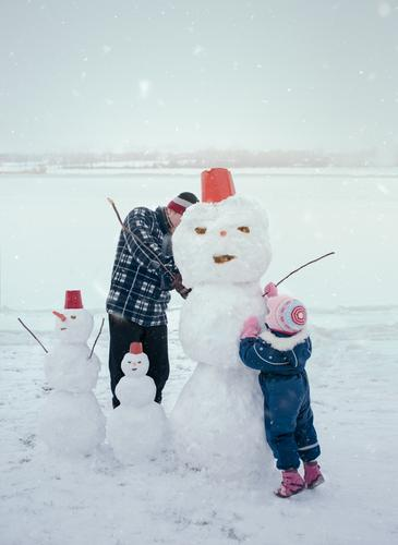 Man and his little daughter making a snowman, spending time together outdoors, having fun on snow in wintertime Lifestyle Joy Happy Leisure and hobbies Playing