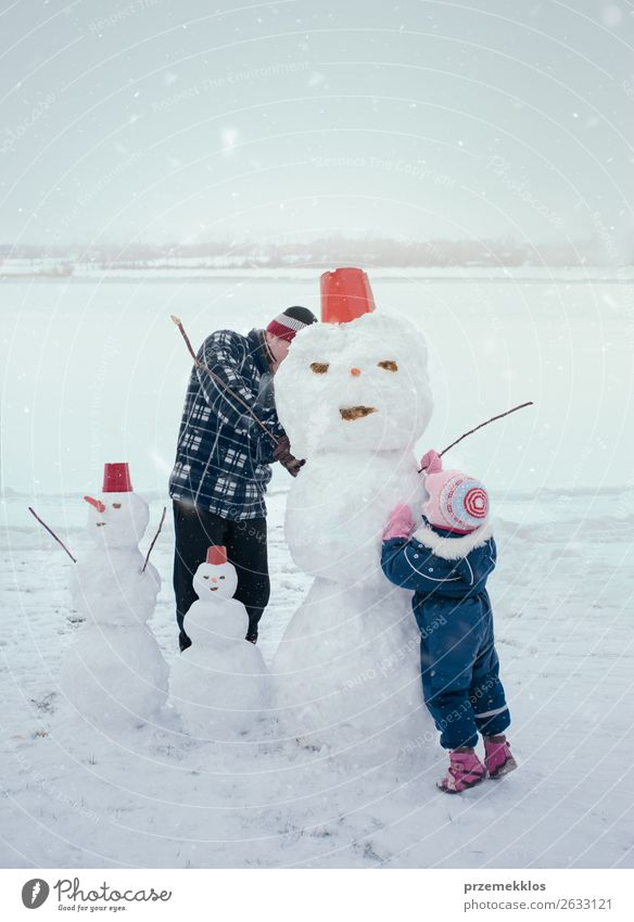 Man and little girl making a snowman Lifestyle Joy Happy Leisure and hobbies Playing Winter Snow Winter vacation Child Human being Girl Adults Parents Father