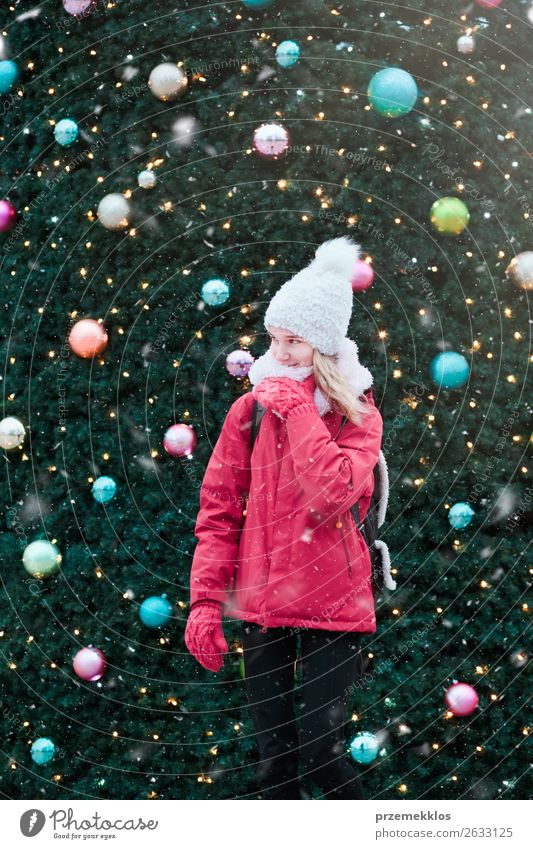 Young girl standing at front of big Christmas tree Lifestyle Joy Winter Snow Decoration Christmas & Advent Human being Young woman Youth (Young adults) Snowfall
