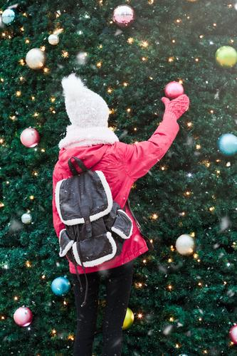 Young girl standing at front of big Christmas tree Lifestyle Joy Winter Snow Decoration Christmas & Advent Human being Young woman Youth (Young adults) 1 Tree
