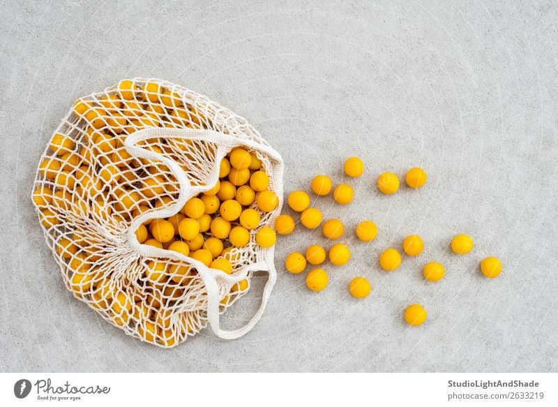 Lots of yellow plums in a mesh shopping bag Food Fruit Nutrition Lifestyle Shopping Summer Gardening Nature Autumn Concrete Simple Fresh Bright Hip & trendy