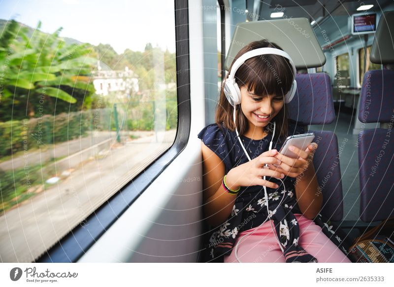 Little girl with headphones and smart phone travelling by train Joy Happy Beautiful Leisure and hobbies Vacation & Travel Trip Music Child Headset PDA
