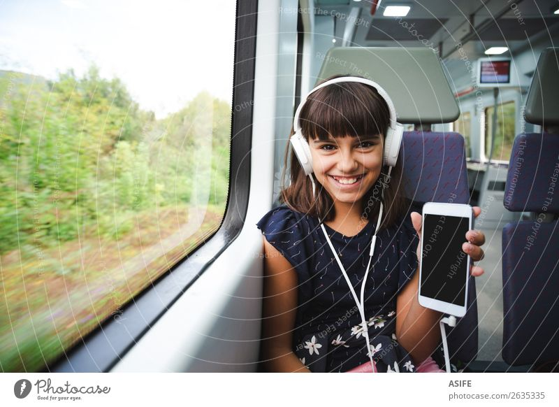 She is happy with her smart phone travelling by train Joy Happy Beautiful Leisure and hobbies Vacation & Travel Trip Music Child Headset PDA Screen Technology