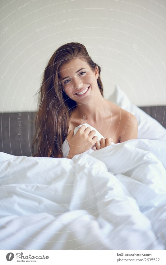 Beautiful girl sitting in bed in white linens Happy Relaxation Bedroom Woman Adults 1 Human being 18 - 30 years Youth (Young adults) Brunette Smiling Sleep