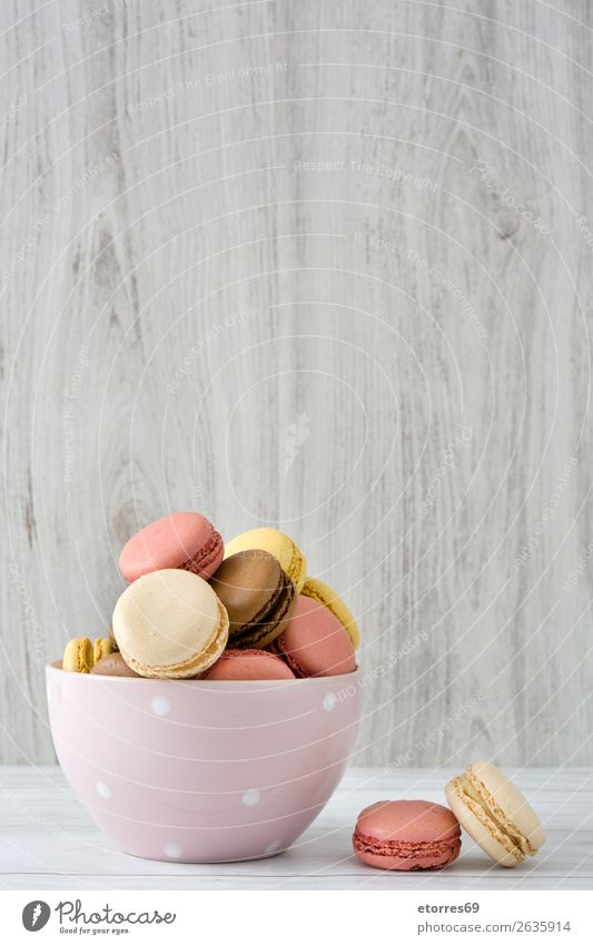 Colorful macarons in a bow on white wooden table Macaron Strawberry Lemon Dessert Coffee Yellow Chocolate Confectionary Raspberry Tradition Candy