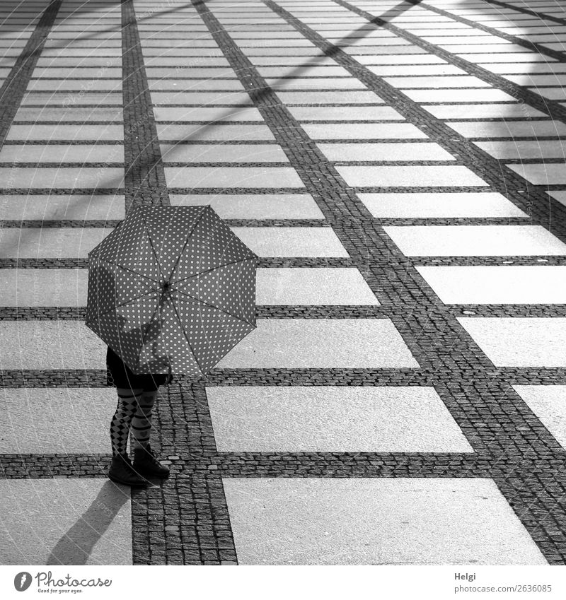 Woman standing in the backlight behind an open umbrella on a large square with plaid floor Human being Feminine Legs feet 1 45 - 60 years Adults Chemnitz Town
