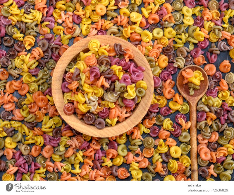 multicolored spiral raw pasta fusilli in a wooden bowl Dough Baked goods Nutrition Dinner Diet Bowl Spoon Wood Eating Fresh Brown Yellow Green Red Colour