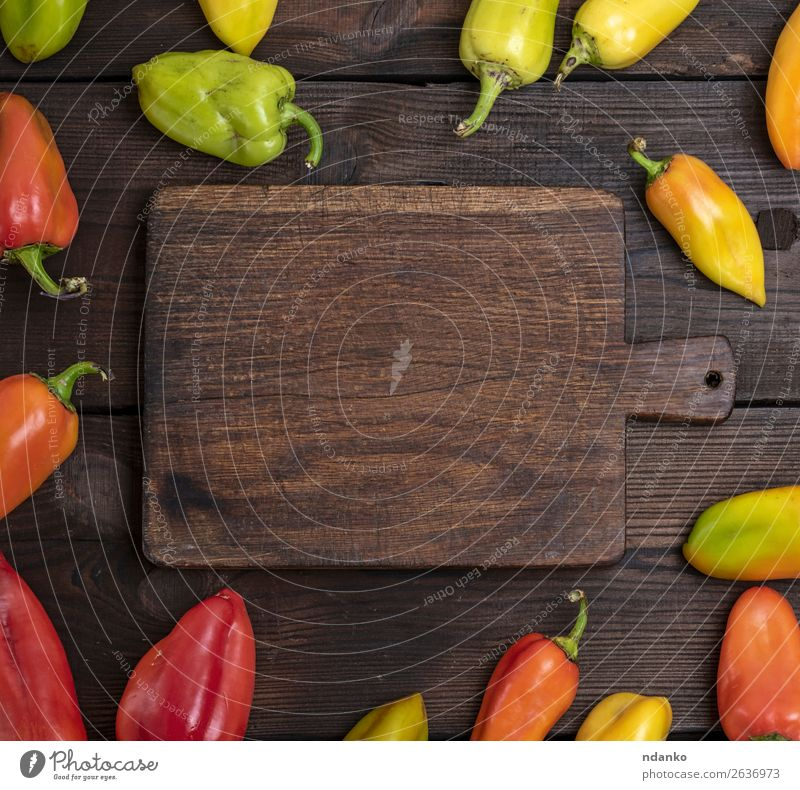 fresh green, yellow and red peppers Vegetable Nutrition Vegetarian diet Table Kitchen Wood Fresh Natural Brown Yellow Green Red Colour Chopping board