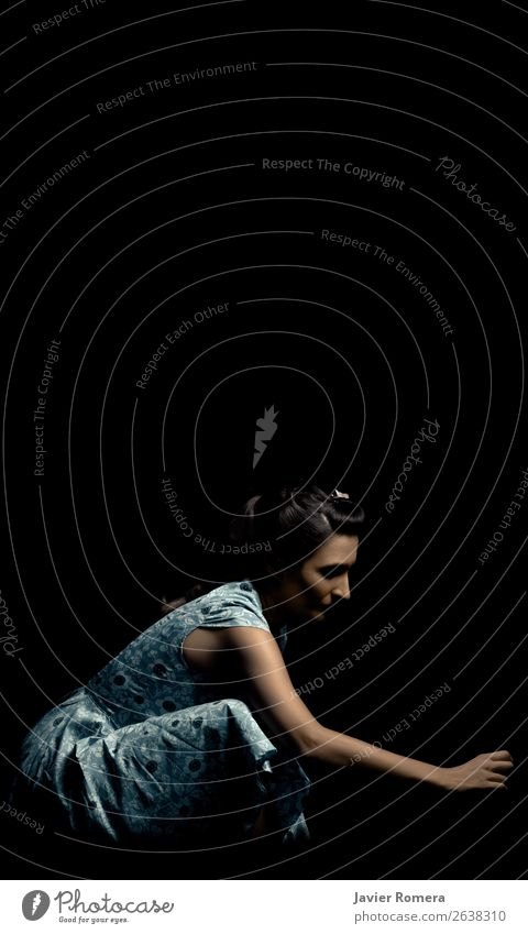 Woman crouched in a blue dress. Young woman Youth (Young adults) Dress Sadness Dark Retro Blue Black Caution Concern Longing Loneliness Guilty Claustrophobia