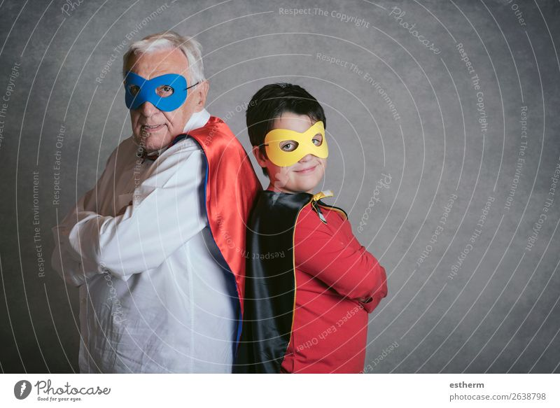 Grandfather With Grandson dressed as a superhero on gray background Lifestyle Joy Adventure Feasts & Celebrations Carnival Fairs & Carnivals Success Retirement