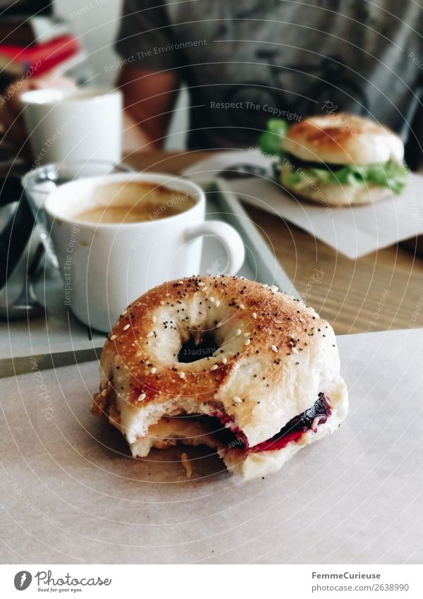 Two people having breakfast bagels in a cafe Lifestyle Young man Youth (Young adults) Man Adults 1 Human being To enjoy Bagel bitten off Coffee Café Breakfast