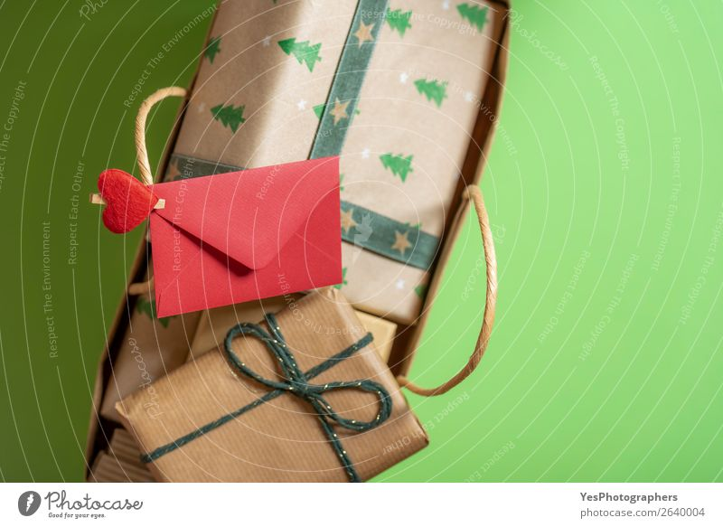 Red envelope clipped on the handle from a full of gifts bag. Feasts & Celebrations Christmas & Advent Paper Happiness Green Surprise Tradition above view