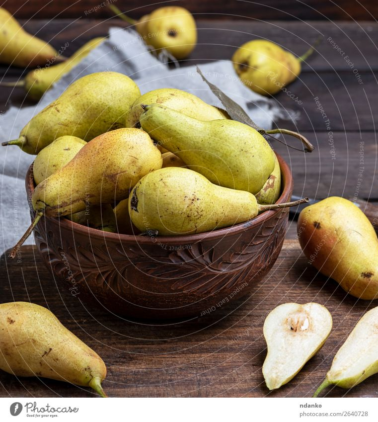 ripe green pears in a brown clay bowl Fruit Nutrition Vegetarian diet Diet Bowl Table Nature Autumn Wood Old Eating Fresh Delicious Natural Above Juicy Yellow