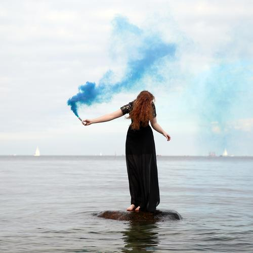 nina Feminine Woman Adults 1 Human being Water Sky Horizon Coast Baltic Sea Dress Red-haired Long-haired Curl Torch Smoke Movement To hold on Stand Maritime