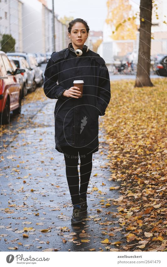 young woman walking along city street in autumn Drinking Hot drink Coffee Mug Lifestyle Style Leisure and hobbies Human being Feminine Young woman